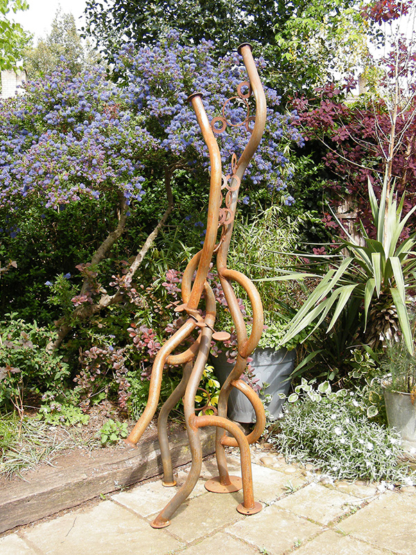 Serpentine sculpture viewed in artist's garden