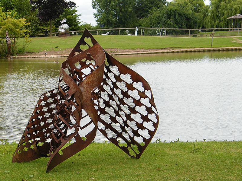 Metal sculpture title Trinity viewed by lake